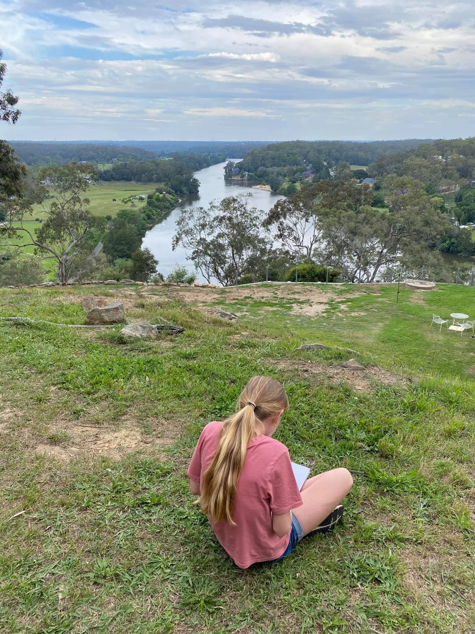 Girl sitting alone at the Brewongle lookout with her back to the camera and the river behind her