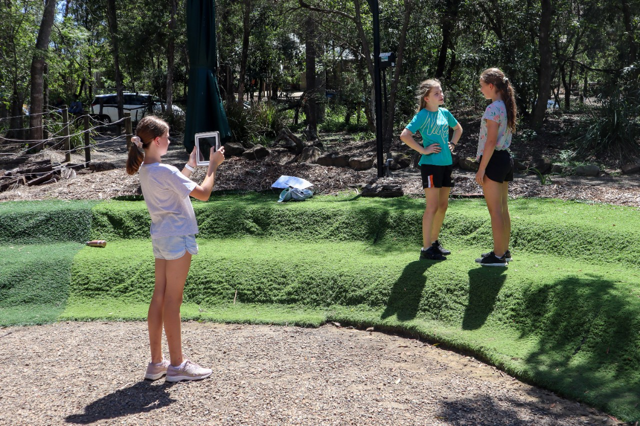 image of 3 students filming a scene with an ipad