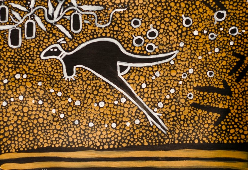 Aboriginal artwork in earthy browns and yellows depicting a hopping kangaroo and gum nuts.
